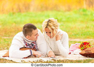 couple on a picnic together reading a novel