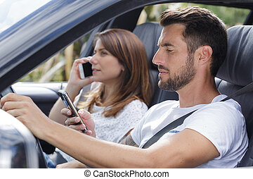 couple on a road trip looking at phone