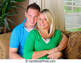 Couple On A Sofa - Attractive Couple Sitting On A Sofa At...