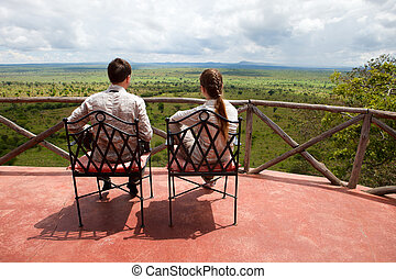 Couple on balcony of safari lodge - Young couple observing...