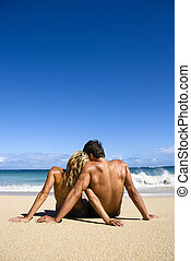 Couple on beach. - Couple sitting close together on Maui,...