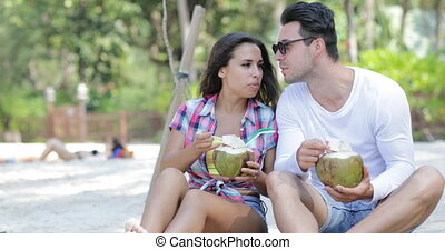 Couple On Beach Drink Coconut Cocktail Talking Sit Under Palm Trees, Happy Man And Woman Tourists Communication