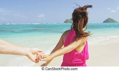 Couple on beach running having fun on honeymoon on Hawaii. Romantic couple joyful and full of happiness on travel vacation on Lanikai beach, Oahu, Hawaii, USA. Asian woman, Caucasian man. RED EPIC.