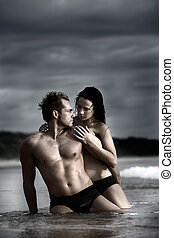 Couple on beach - Sexy couple on beach with dark stormy...