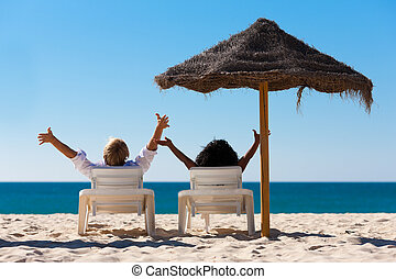 Couple on beach vacation with sunshade - Couple sitting in...