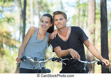couple on bicycles rides on the road