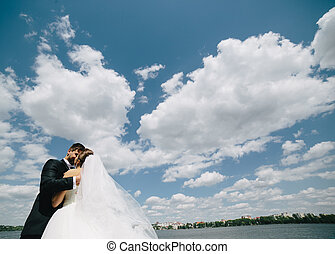 couple on blue sky background, water