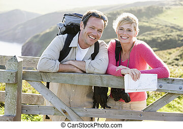 Couple on cliffside outdoors leaning on railing and smiling