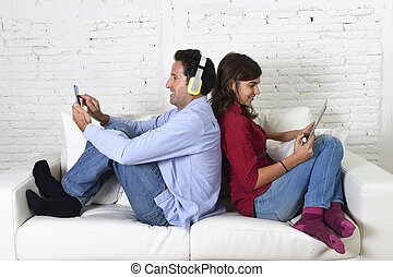couple on couch ignoring each other using mobile phone and digital tablet in internet addiction
