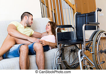 Couple on couch near wheelchair
