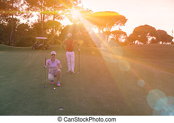 couple on golf course at sunset