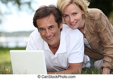 Couple on grass with computer