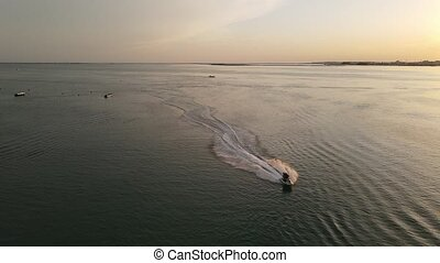 Couple on motor boat enjoying sunset, speed and water in ...