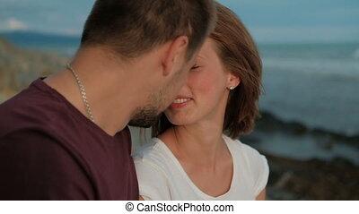 Couple on photo shoot on seaside walking, kissing, enjoy moments