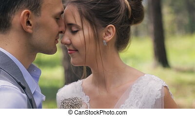 Couple on photo shoot with hedgehogs in hands kissing in wedding day