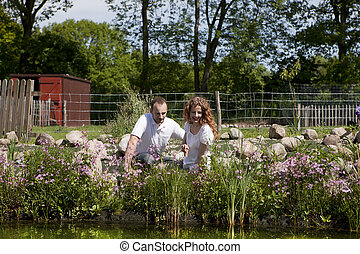 couple on pink flowered garden pond, summer, trees in...