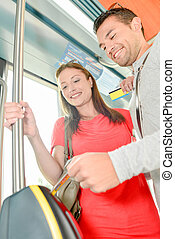 Couple on public transport, entering ticket in machine