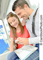 Couple on public transport, looking at photos on digital camera