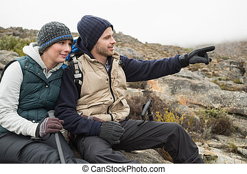 Young couple sitting on rock with backpack and trekking poles while on a hike