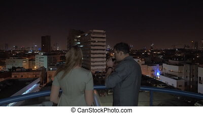 Couple on rooftop looking at night Tel Aviv and having...
