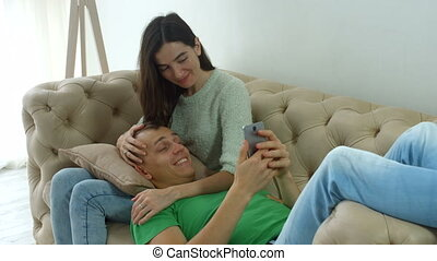 Couple on sofa enjoying media content in smartphone
