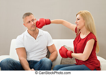 Couple On Sofa Fighting With Boxing Gloves