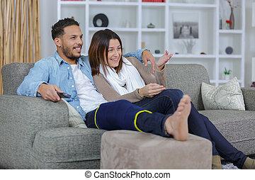 Couple on sofa, man wearing leg support