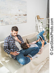 couple on sofa using devices