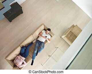 couple on sofa using mobile phones top view