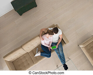 couple on sofa using tablet computer top view