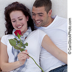 Couple on sofa with a rose