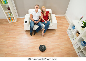 Couple On Sofa With Robotic Vacuum Cleaner On Floor