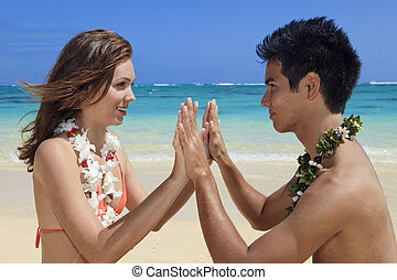couple on the beach in hawaii meditating