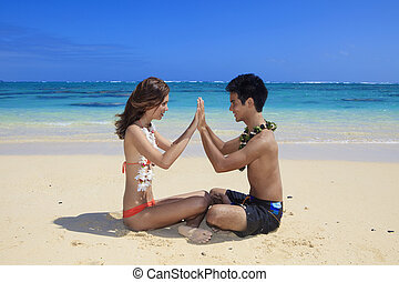 couple on the beach in hawaii meditating