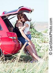 couple on the beach on a red car