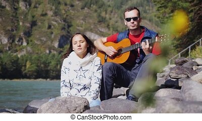 Couple on the beach playing guitar sings song on a summer day next to mountain river. 1920x1080