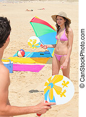 couple on the beach playing rackets