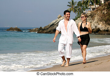 Couple on the beach - Young couple walking on the beach
