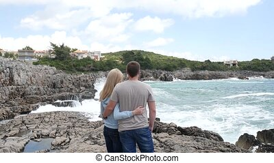 Couple on the rocky shore. Boy and girl hugging on the rocks. To