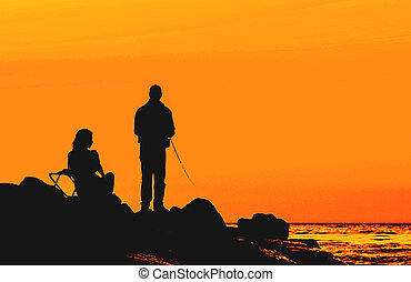 couple on the sunset rocky shore