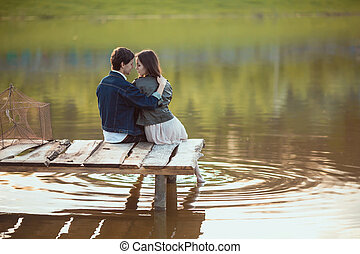 Couple on the wooden jetty at a lake