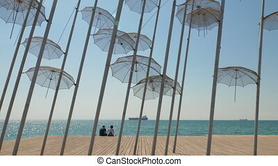 Couple on waterfront with Umbrellas sculpture. Thessaloniki,...