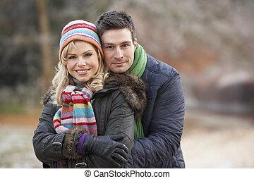 Couple On Winter Walk Through Frosty Landscape