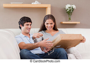 Couple opening parcel on the couch - Young couple opening...