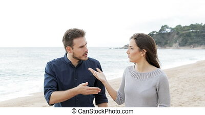 Couple or friends arguing on the beach