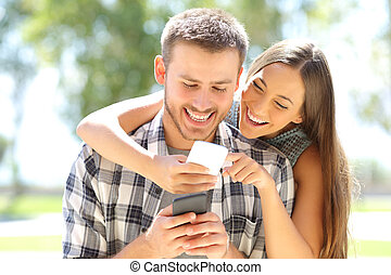 Couple or friends laughing with phones