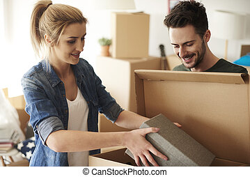 Couple organizing stuff from cardboard boxes