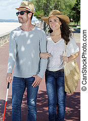 couple out for a walk man is visually impaired