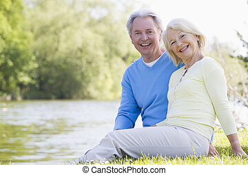 Couple outdoors at park by lake smiling