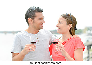 Couple outdoors drinking a glass of red wine